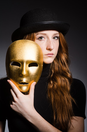 Redhead woman in hat  iwith mask in hypocrisy consept against grey background photo