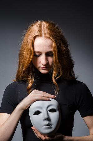 hipocres�a: Redhead mujer m�scara iwith en consept hipocres�a contra el fondo gris