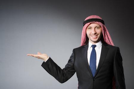 qameez: Arab businessman holding hands against grey background Stock Photo