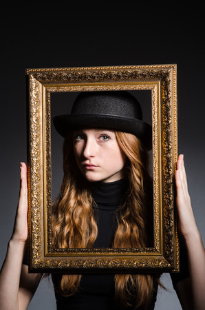 Redhead with picture frame against dark background photo