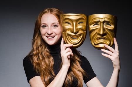 hypocrisy: Redhead woman iwith masks in hypocrisy consept against grey background