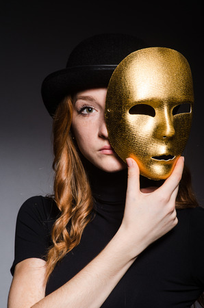 impostor: Redhead woman in hat  iwith mask in hypocrisy consept against dark  grey background