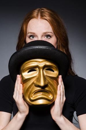 hipocres�a: Mujer del Redhead en sombrero iwith m�scara en el sombrero en consept hipocres�a contra el fondo gris