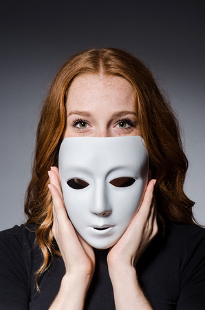 Redhead woman iwith mask in hypocrisy consept against grey background photo