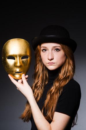 hipocres�a: Mujer del Redhead en sombrero iwith m�scara en consept hipocres�a contra el fondo gris oscuro