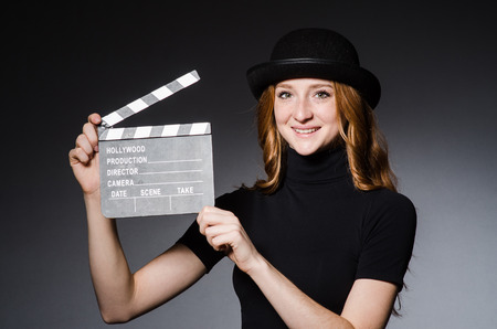 Young redhead girl in hat with movie board against grey background