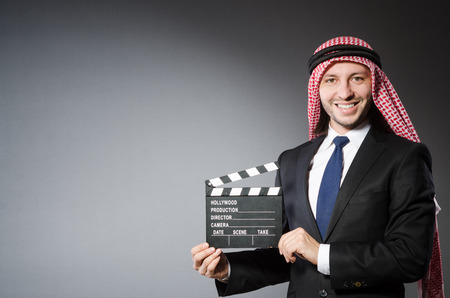 Arab man with movie clapper isolated on white photo