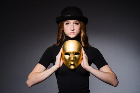 hipocresía: Mujer del Redhead en sombrero iwith m�scara en consept hipocres�a contra el fondo gris Foto de archivo