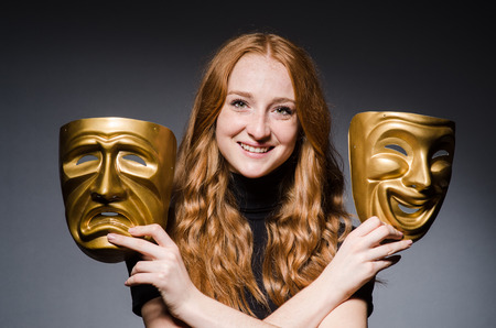 insincere: Redhead woman iwith masks in hypocrisy consept against grey background