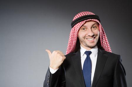 qameez: Arab businessman in delight against grey background Stock Photo