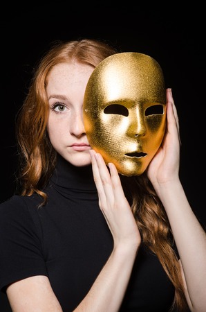 Redhead woman iwith mask in hypocrisy consept against black  background photo