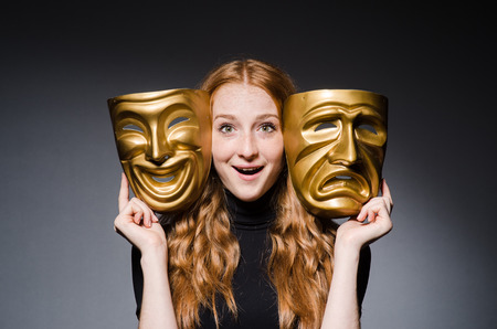 Redhead woman iwith masks in hypocrisy consept against grey background photo