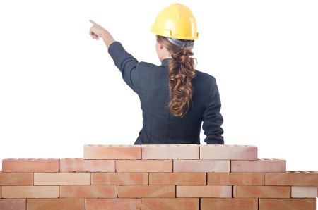 Young female builder near brick wall photo