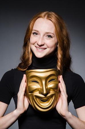 hipocresía: Redhead mujer m�scara iwith en consept hipocres�a contra el fondo gris