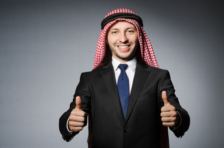 bohra: Arab businessman with thumbs up againt grey background