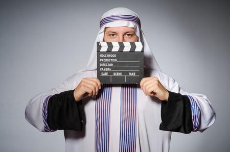qameez: Arab businessman with movie board Stock Photo