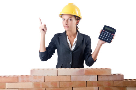 Woman construction worker with calculator on white photo