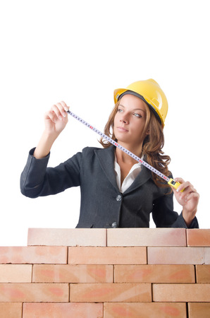 Woman builder measuring isolated on the white photo