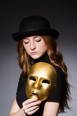 Redhead woman in hat  iwith mask in hypocrisy consept against grey