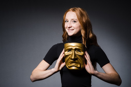 hypocrisy: Redhead woman iwith mask in hypocrisy consept against grey  Stock Photo
