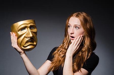 hipocres�a: Mujer del Redhead iwith m�scara en consept hipocres�a contra el fondo gris