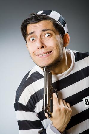 escaping: Prisoner with gun against dark background Stock Photo
