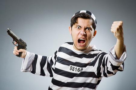 Prisoner with gun against dark background photo
