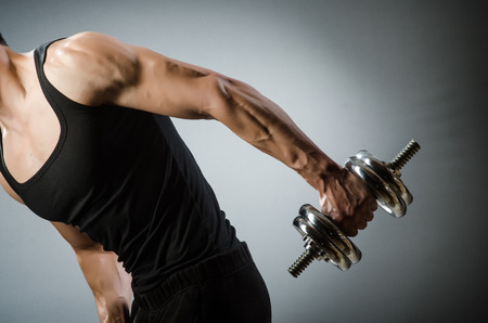 tricep: Muscular ripped bodybuilder with dumbbells Stock Photo