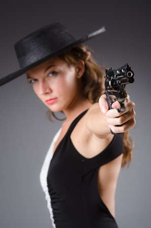 Woman with gun against dark background photo