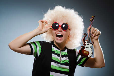 afrocut: Funny man with miniature guitar Stock Photo