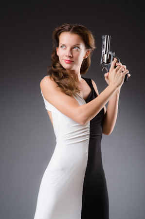 Woman with gun against dark background Stock Photo - 30414481