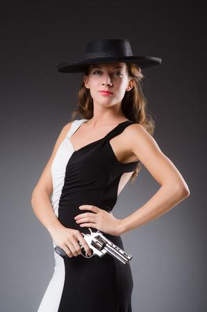 Woman with gun against dark background Stock Photo - 30414479