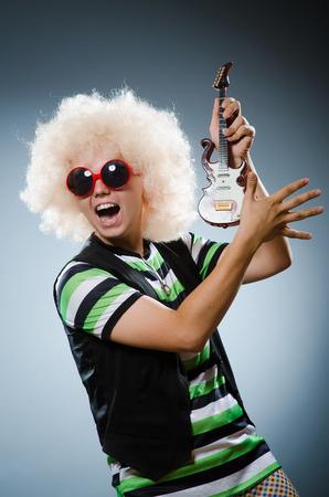 afrocut: Funny man with miniature guitar Stock Photo