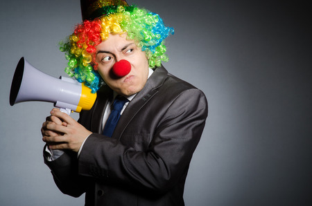 Clown with loudspeaker in funny concept photo