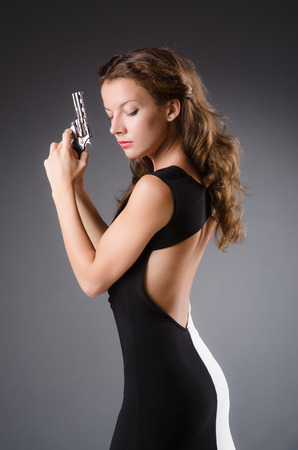 Woman with gun against dark background Stock Photo - 30413968