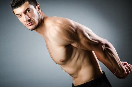tricep: Muscular man posing in dark studio