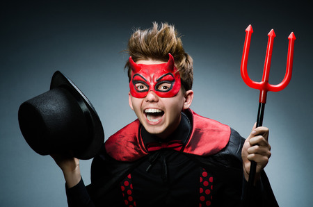 Funny devil against dark background photo