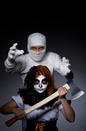 Halloween concept with mummy and woman with axe photo