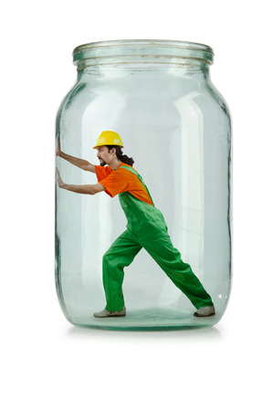 imprisoned: Man in coveralls imprisoned in glass jar Stock Photo