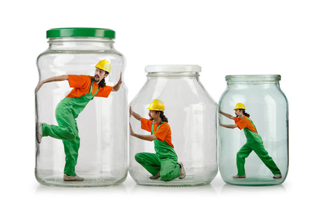 confined space: Man in coveralls imprisoned in glass jar Stock Photo