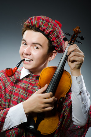 Funny scotsman with violin fiddle photo