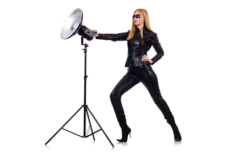 barndoors: Woman in black leather dress in studio shootout Stock Photo