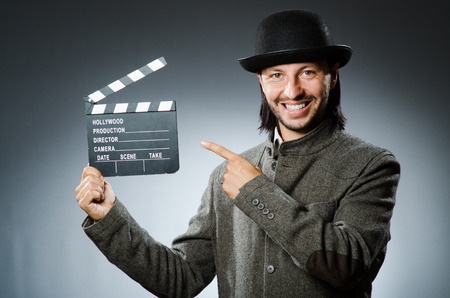 clapperboard: Man with movie clapperboard and hat