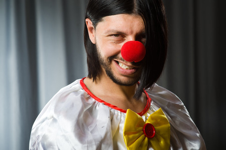 disillusioned: Sad clown against grey background
