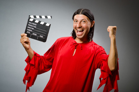 clapboard: Man in red dress with movie clapboard