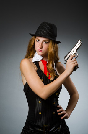 Woman gangster with gun in hand photo