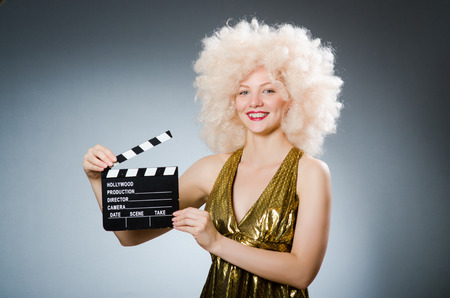 afrocut: Blond woman with movie board