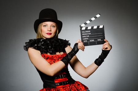Woman with movie clapboard against grey background photo