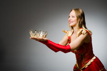 Queen in red costume against dark background photo