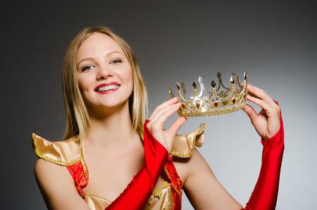 Queen in red costume against dark background photo